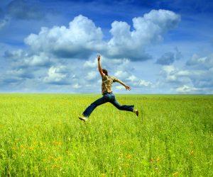 man-jumps-in-green-field-against-blue-sky
